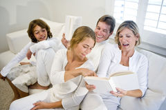 Familia que se sienta en el sofá mientras que la madre lee el libro Fotografía de archivo libre de regalías
