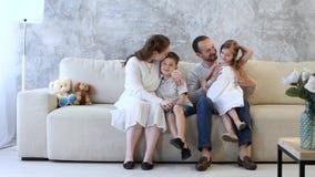 Familia que se sienta en el sofá y hablar almacen de metraje de vídeo