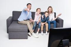 Familia que se sienta en el sofá y que muestra los pulgares abajo mientras que ve la TV junto Fotos de archivo libres de regalías