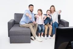 Familia que se sienta en el sofá y que muestra los pulgares abajo mientras que ve la TV junto Imágenes de archivo libres de regalías