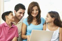 Familia que se sienta en el sofá en el país con la computadora portátil Foto de archivo libre de regalías