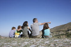 Familia que se sienta en el top de la montaña Imágenes de archivo libres de regalías