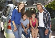 Familia que se sienta en el tronco del coche Fotografía de archivo