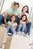 Familia que se sienta en escalera con los rectángulos en nuevo hogar Foto de archivo