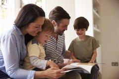 Familia que se sienta en historia de la lectura de Seat de ventana en casa junto imagen de archivo