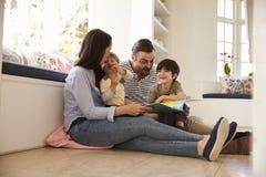 Familia que se sienta en historia de la lectura del piso en casa junto imagenes de archivo