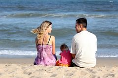 Familia que se sienta en la arena Imagen de archivo