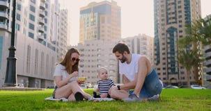 Familia que se sienta en la hierba en la ciudad que ríe con un pequeño niño metrajes