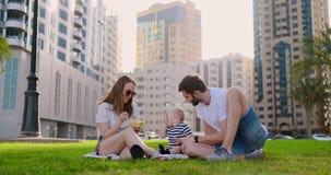 Familia que se sienta en la hierba en la ciudad que r?e con un peque?o ni?o almacen de metraje de vídeo