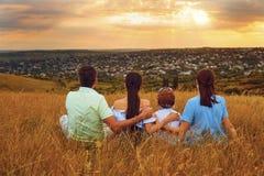 Familia que se sienta en la naturaleza que mira puesta del sol hermosa Imagenes de archivo