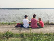Familia que se sienta en la orilla del lago Fotos de archivo libres de regalías