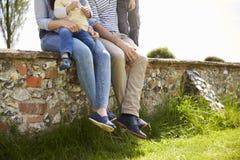 Familia que se sienta en la pared durante paseo en campo del verano imágenes de archivo libres de regalías