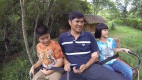 Familia que se sienta en la parte posterior de un elefante almacen de metraje de vídeo