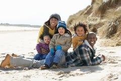 Familia que se sienta en la playa del invierno Foto de archivo