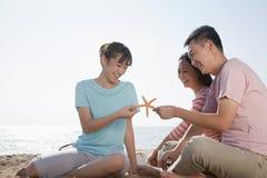 Familia que se sienta en la playa por el océano que sostiene una estrella de mar Foto de archivo libre de regalías
