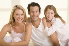 Familia que se sienta en la sonrisa de la cama Fotos de archivo libres de regalías