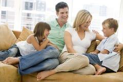 Familia que se sienta en la sonrisa de la sala de estar Imagen de archivo libre de regalías
