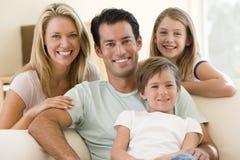Familia que se sienta en la sonrisa de la sala de estar Imágenes de archivo libres de regalías