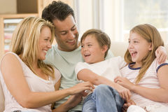Familia que se sienta en la sonrisa de la sala de estar