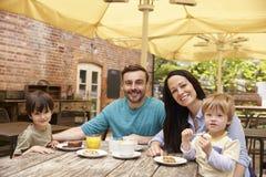 Familia que se sienta en la tabla al aire libre del café que almuerza imagenes de archivo