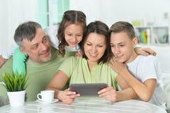 Familia que se sienta en la tabla con la tableta Fotos de archivo libres de regalías