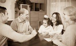 Familia que se sienta en la tabla con las tarjetas Imagenes de archivo
