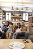 Familia que se sienta en la televisión de observación de Sofa In Open Plan Lounge Imagen de archivo