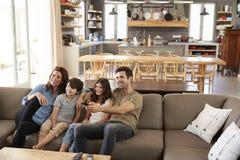 Familia que se sienta en la televisión de observación de Sofa In Open Plan Lounge Imagen de archivo libre de regalías