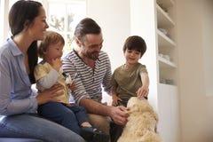 Familia que se sienta en la ventana Seat en casa con golden retriever fotos de archivo libres de regalías