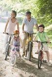 Familia que se sienta en las bicis en la sonrisa del camino Imagen de archivo