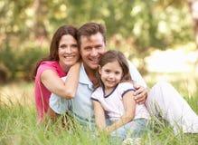 Familia que se sienta en parque Imagenes de archivo
