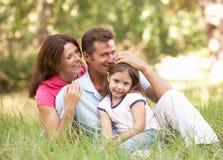 Familia que se sienta en parque Foto de archivo