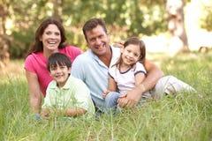 Familia que se sienta en parque Fotografía de archivo libre de regalías