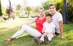 Familia que se sienta en prado verde Foto de archivo