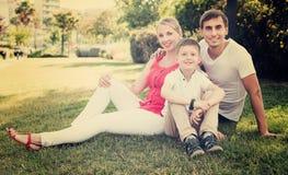 Familia que se sienta en prado verde Fotografía de archivo