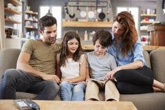 Familia que se sienta en Sofa In Lounge Reading Book junto Fotografía de archivo libre de regalías