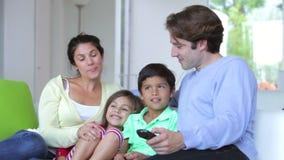 Familia que se sienta en Sofa Watching TV junto almacen de video