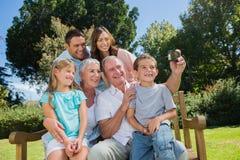 Familia que se sienta en un banco que toma la foto de ellos mismos Imagenes de archivo