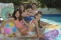 Familia que se sienta junto en The Edge de la piscina Imágenes de archivo libres de regalías