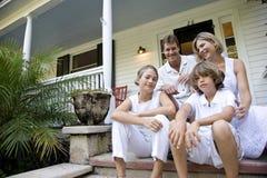 Familia que se sienta junto en pasos de progresión del pórche de entrada Foto de archivo libre de regalías