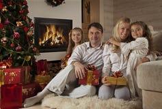 Familia que se sienta por el árbol de navidad Imágenes de archivo libres de regalías