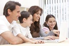 Familia que se sienta usando el ordenador portátil en el país imagenes de archivo