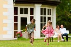 Familia que se sienta y que juega delante de su hogar Foto de archivo libre de regalías