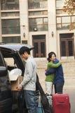 Familia que se traslada a su hijo a dormitorio en campus de la universidad Imagen de archivo libre de regalías