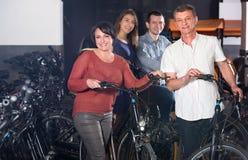 Familia que selecciona las bicis eléctricas en el alquiler Imagen de archivo