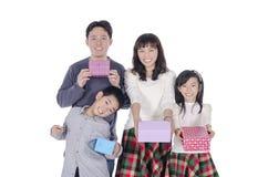 Familia que sonríe sosteniendo el regalo Fotos de archivo libres de regalías