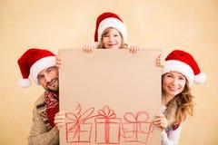 Familia que sostiene el cartel de la Navidad Imagenes de archivo