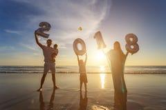Familia que sostiene el globo 2018 del número en la playa en el ti de la puesta del sol Foto de archivo
