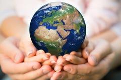 Familia que sostiene el planeta de la tierra Foto de archivo
