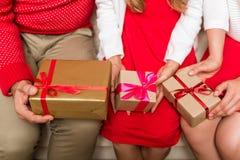 Familia que sostiene los regalos de la Navidad Imagenes de archivo